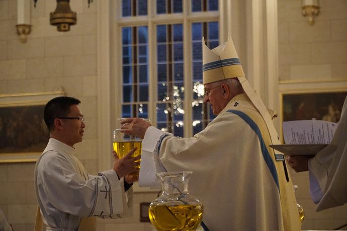 Deacon Kien Nguyen presented the sacred chrism to Archbishop Kurtz.