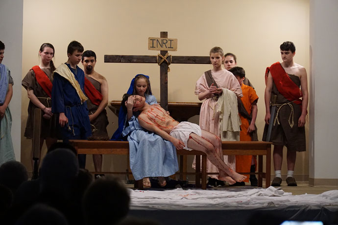 Eighth-grade students at John Paul II Academy, under the direction of Father William P. Burks, held a presentation of the Passion on Good Friday. Jesus, portrayed by Omar Luna, is held by his mother Mother, played by Madeline Minnich, following the depiction of his crucifixion, at right. (Record Photo by Marnie McAllister)