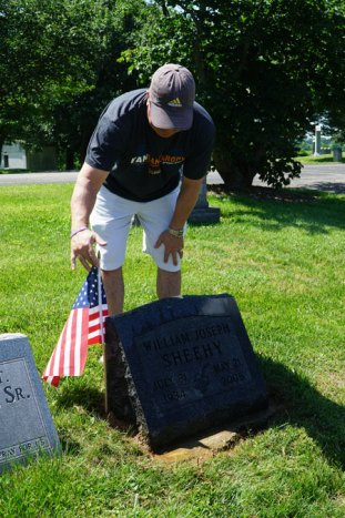 Jim Sheehy placed a flag on the grave of his father, William Joseph Sheehy. William Sheehy attended St. Albert the Great Church.