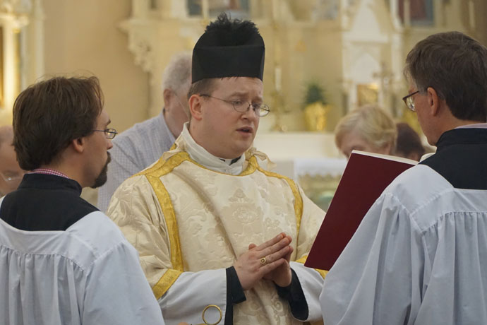 Deacon Jonathan Erdman read from the Gospel of Luke in the center aisle of St. Martin of Tours Church during Mass April 30. Deacon Erdman is the leader of the newly-formed community of Our Lady and St. John. (Record Photo by Ruby Thomas)
