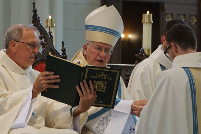 Deacon Nash, left, holds the liturgical book for Archbishop Joseph E. Kurtz at the ordination of Fathers Casey Sanders and Michael Martin May 27. (Record file photo by Jessica Able)