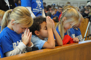 St. Joseph School kindergartners, from left, Mylana Duber, Bradon Saunders and Kennedi Holbert bowed their heads and prayed as Father Terry Bradshaw, pastor of the Basilica of St. Joseph Proto-Cathedral, said a final blessing at the school's Blue Ribbon celebration Nov. 17. (Record Photo by Jessica Able)