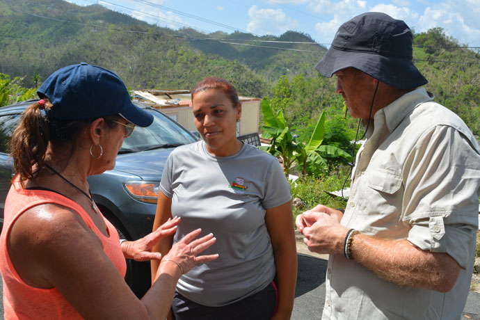 Trinity High School teacher Maria Martin, left, spoke to Yadira Reyes, whose home in Puerto Rico was destroyed by Hurricane Maria. Fellow teacher Chad Waggoner looked on. The Trinity teachers traveled to the island Oct. 25 to 28 with supplies for hurricane survivors. (Photo Special to The Record)