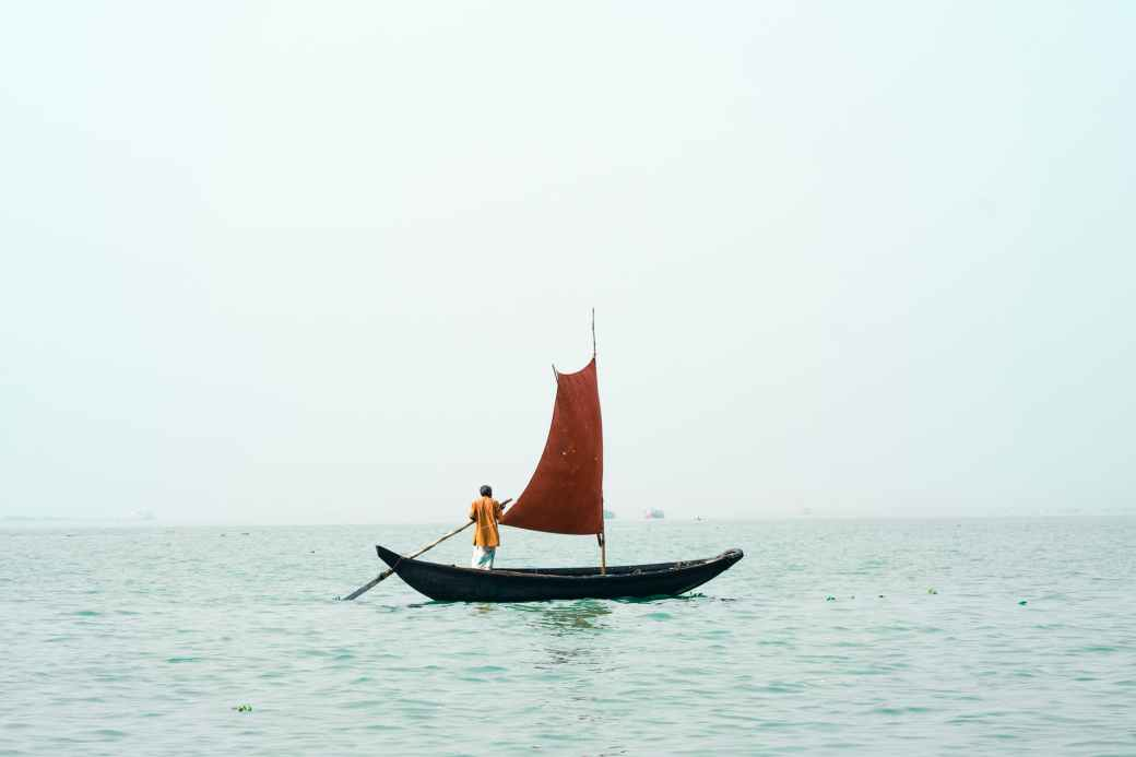 a man rowing a small boat with a sail