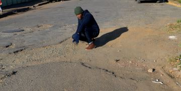 TRAFFIC ALERT: The Rep reporter Bhongo Jacob surveys one of many potholes marring the road surfaces of Komani Picture: ABONGILE SOLUNDWANA