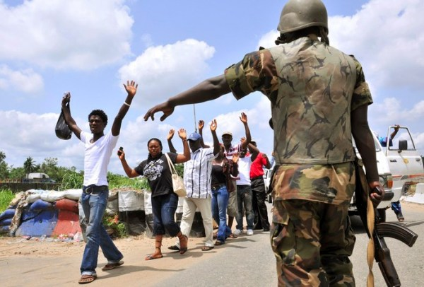 A Nigerian military officer directs civilians at a checkpoint along Sapele-Warr road in the Niger Delta region