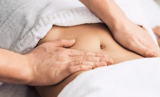 Massage of the stomach in the spa. Cosmetic clinic, spa, wellness center, healthcare concept.