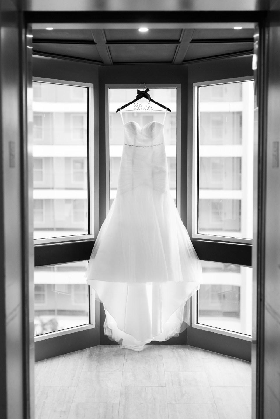Black and White Photo of Wedding Dress Hanging UP