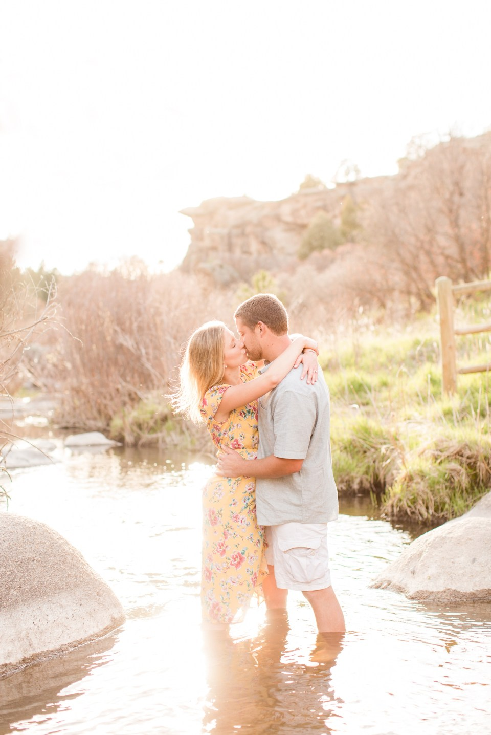 Couple at sunset in a stream at Castlewood State Park in Colorado. Engagement Session in Castlewood State Park.