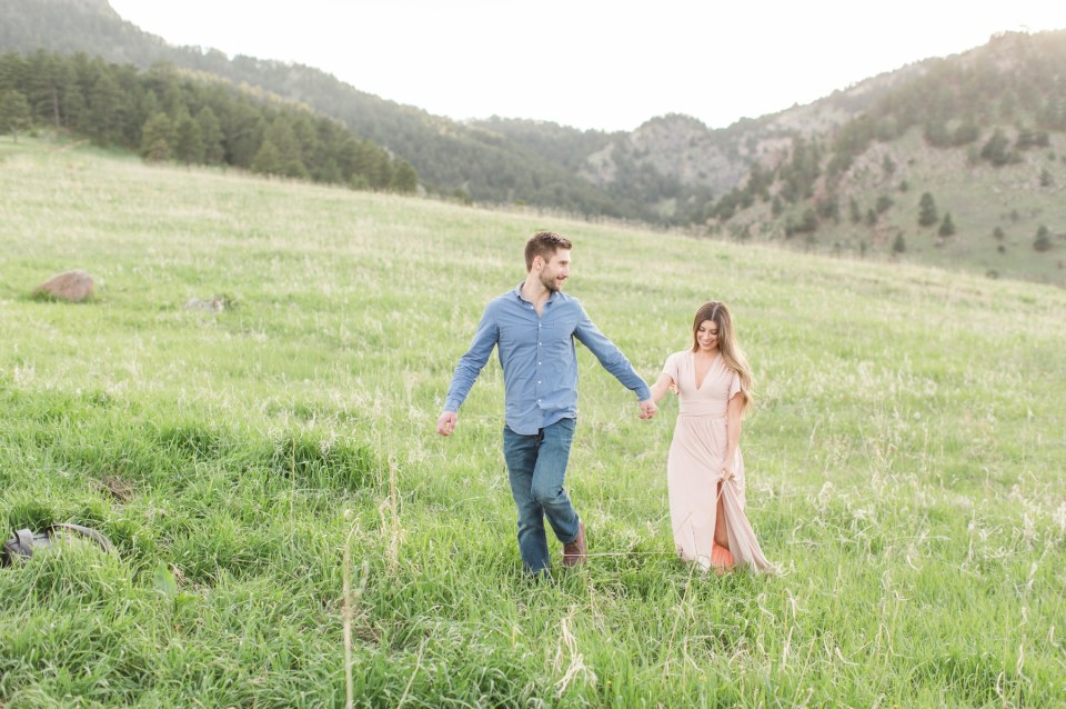 Couple walking hand in hand in a field at chautauqua park in Boulder Colorado