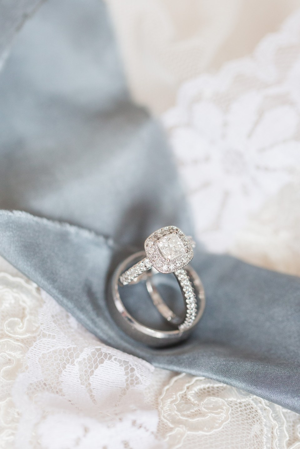 Photo of a halo style engagement ring balancing on a wedding band.