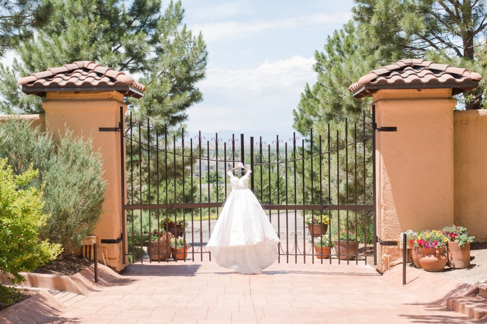 Wedding dress handing on a gate in Parker Colorado at the Villa Parker. Colorado Wedding Photographer.