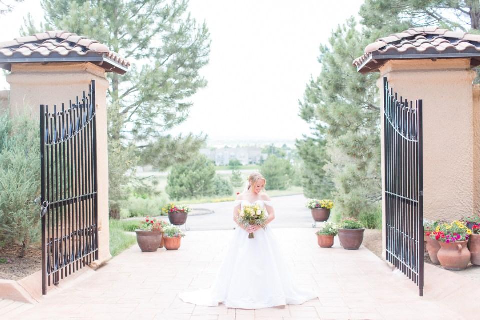 Bride in front of the gates in Villa Parker, Parker Colorado.