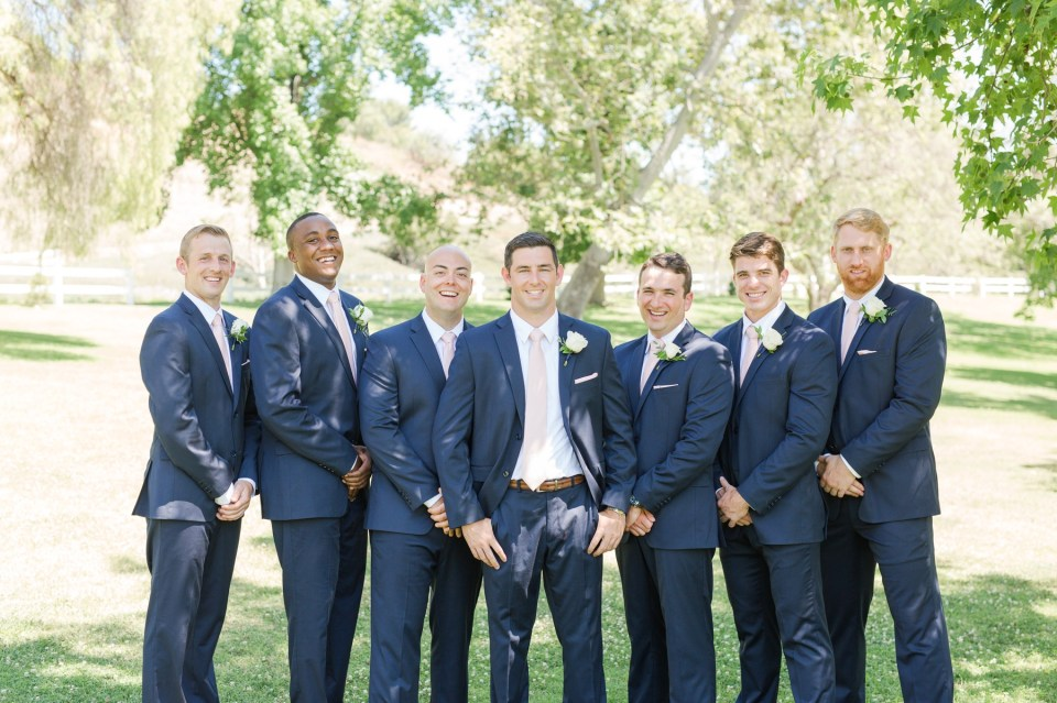 Groom posing with groomsmen in navy suits with blush ties at Coto Valley Country Club.