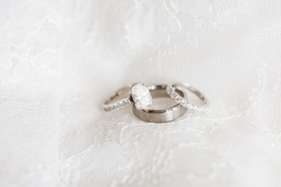 Wedding rings on top of a wedding dress