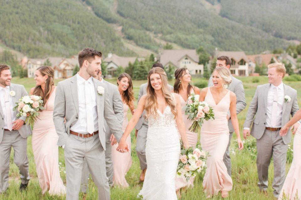 bride and groom casually walking in a field in a Colorado wedding.