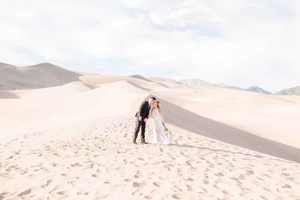 Couple standing at the bottom of the Sand Dunes at Great Sand Dunes National Park