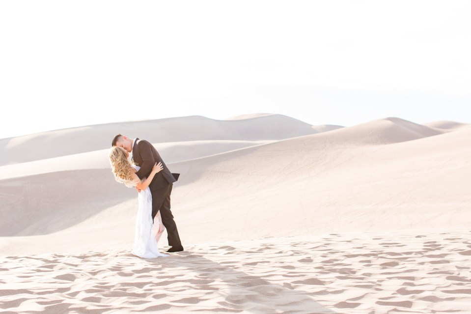 Couple kissing on top of a sand dune at the Great Sand Dunes National Park in Colorado.