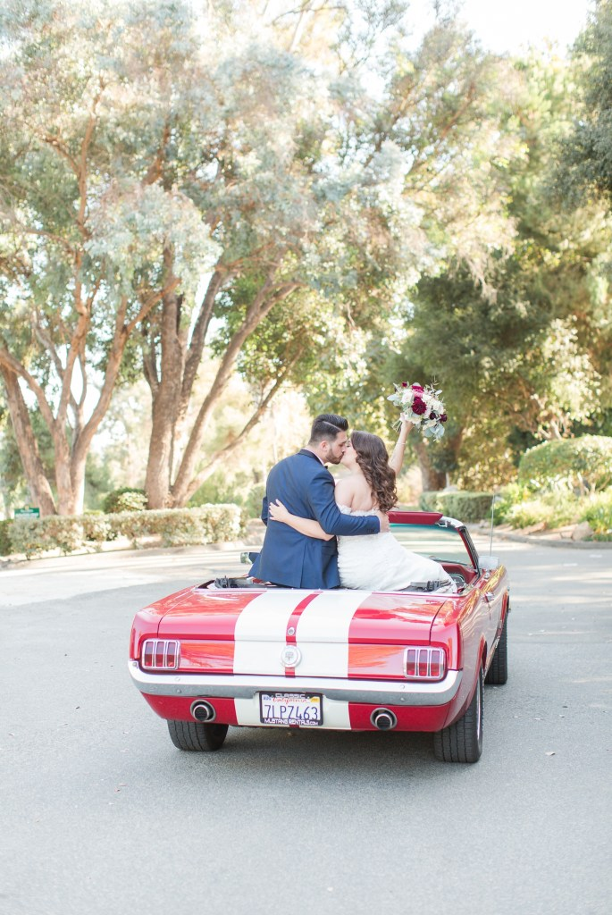 Bride and groom sitting in a red 1966 mustang getaway car.