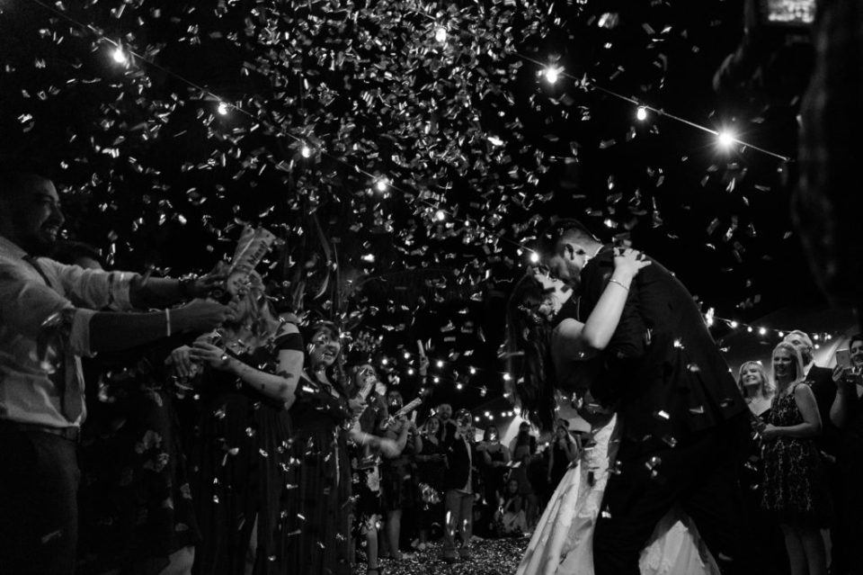 Bride and groom kissing while confetti falls all around them during the wedding reception.