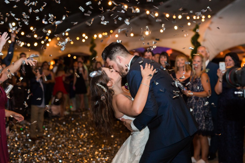 Bride and groom kiss as confetti falls during grand exit. Grand exit wedding ideas.