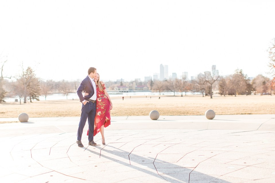 Engagement session at City Park with Denver skyline in the background.
