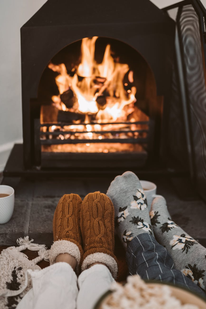 person wearing gray and white socks near brown fireplace