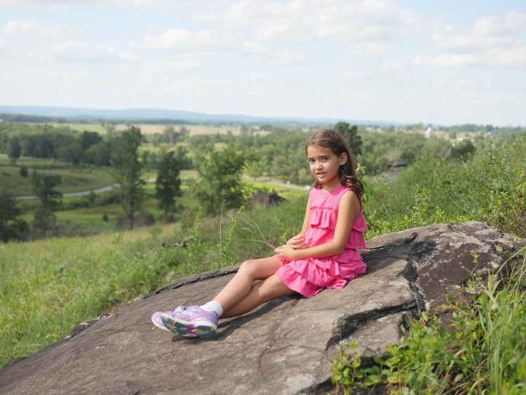 A child appreciates the view of the battlefield at Little Round Top in Gettysburg - Theresa's Reviews