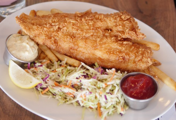 The Fish and Chips are made with whole filet beer battered haddock and served with housemade tartar sauce, french fries and broccoli carrot slaw at Hudson Coastal Raw Bar & Grille - Theresa's Reviews