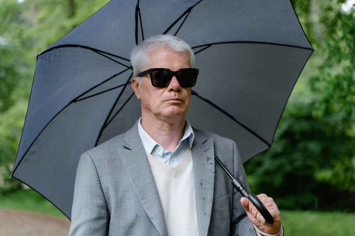 close up shot of an elderly man in gray suit and with sunglasses using an umbrella