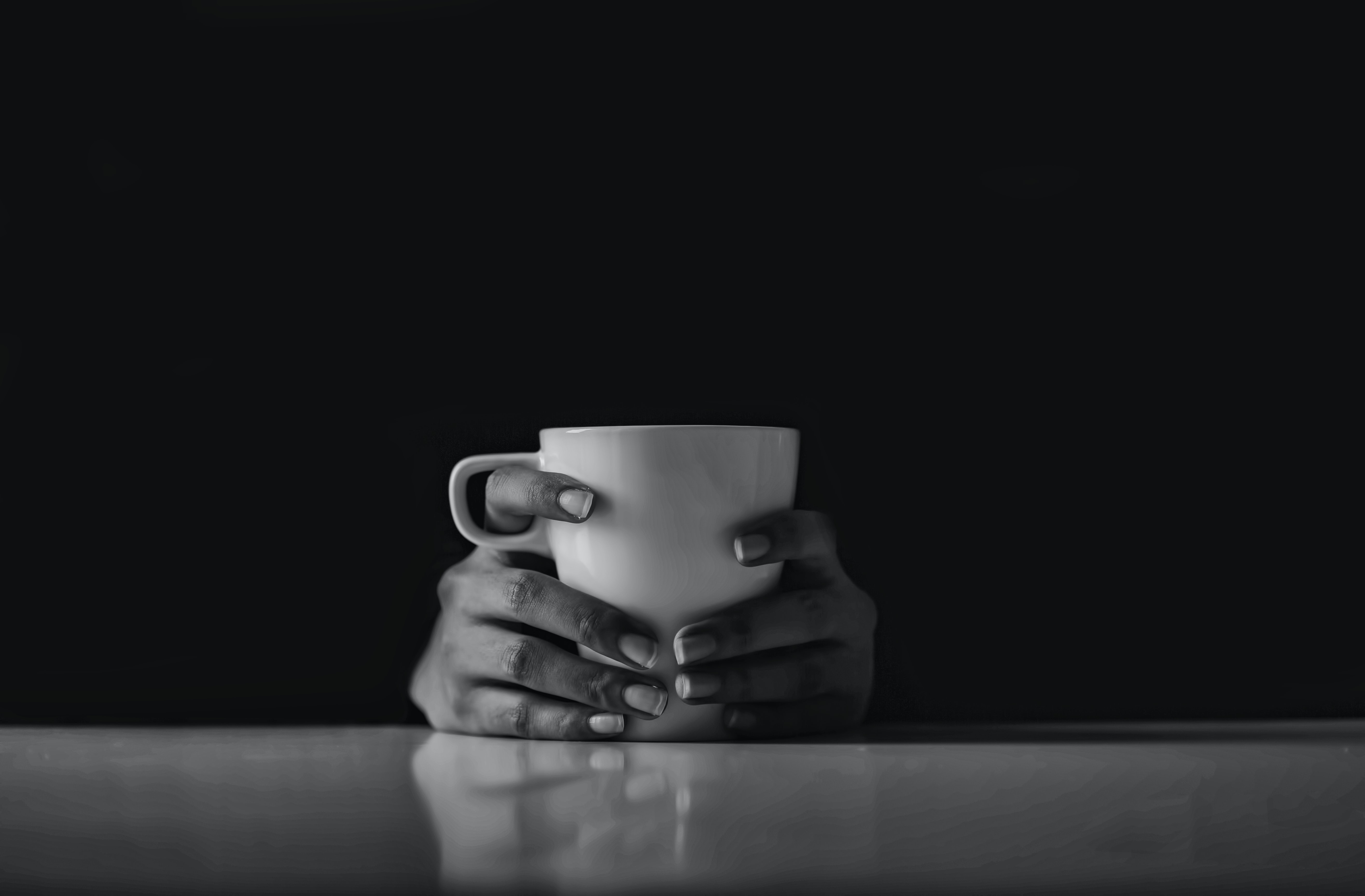 grayscale photo of person's hands holding a ceramic mug