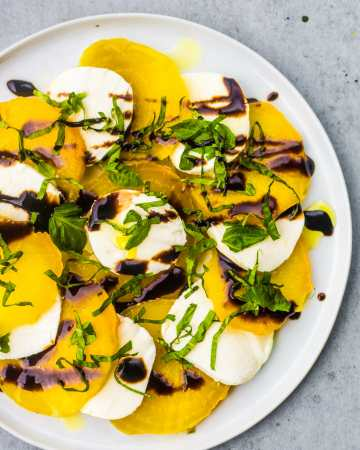 Roasted yellow beets with fresh mozzarella, basil, balsamic reduction, and olive oil.