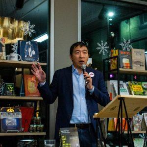 Yang standing at podium