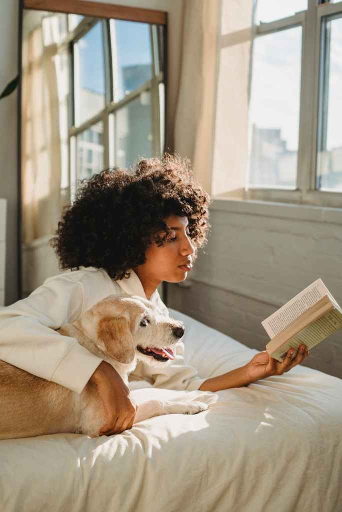 concentrated young black woman cuddling curious obedient dog while reading book ob bed