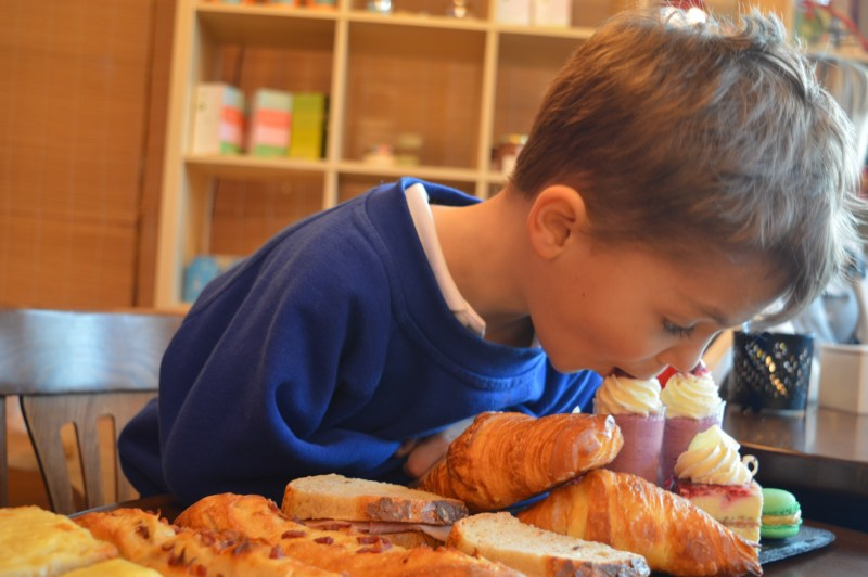 Little boy eating at Delices bakery Bedford