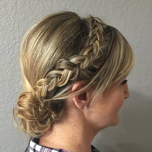 side braid and low bun updo with bangs for women over 40