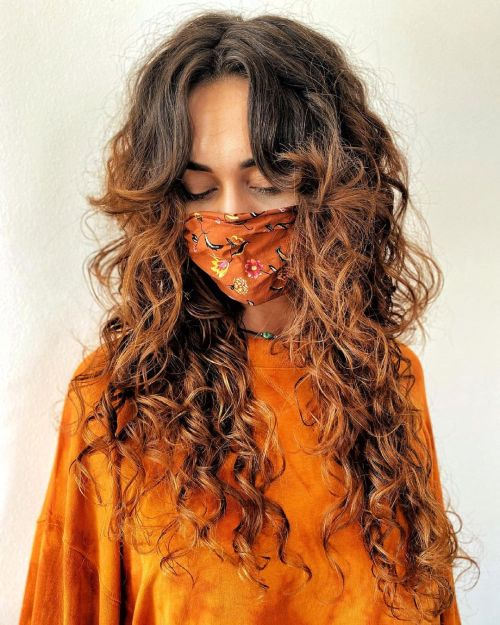 Long Highlighted Curly Hair with Curtain Bangs