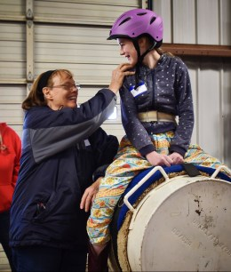 volunteer demonstrating hand hold with child on dummy horse