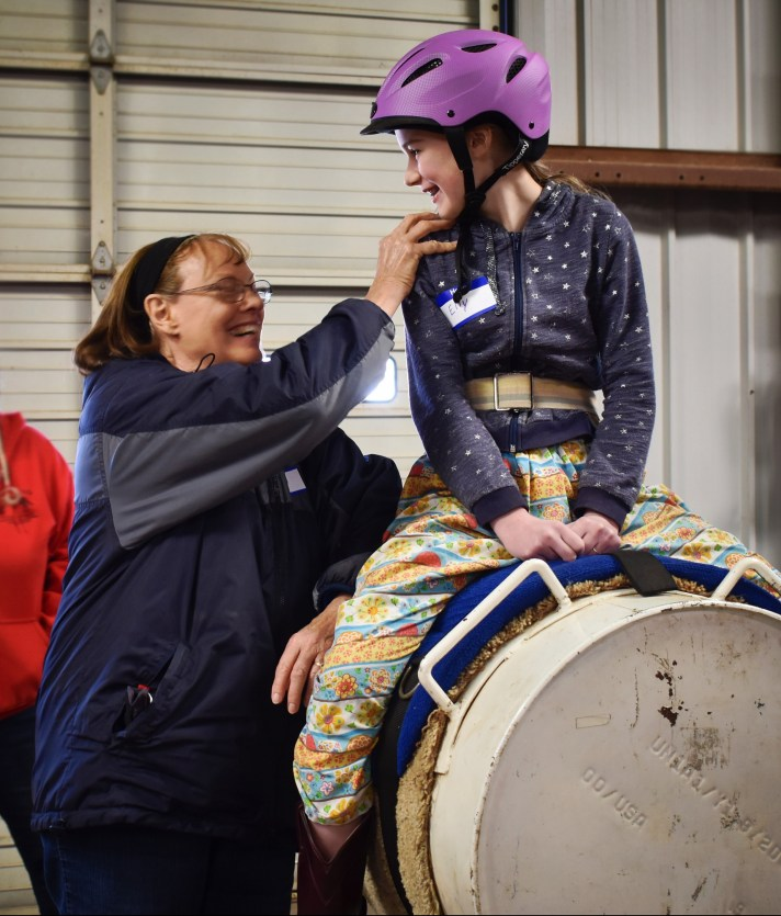 volunteer training hand holds on barrel horse with a student rider