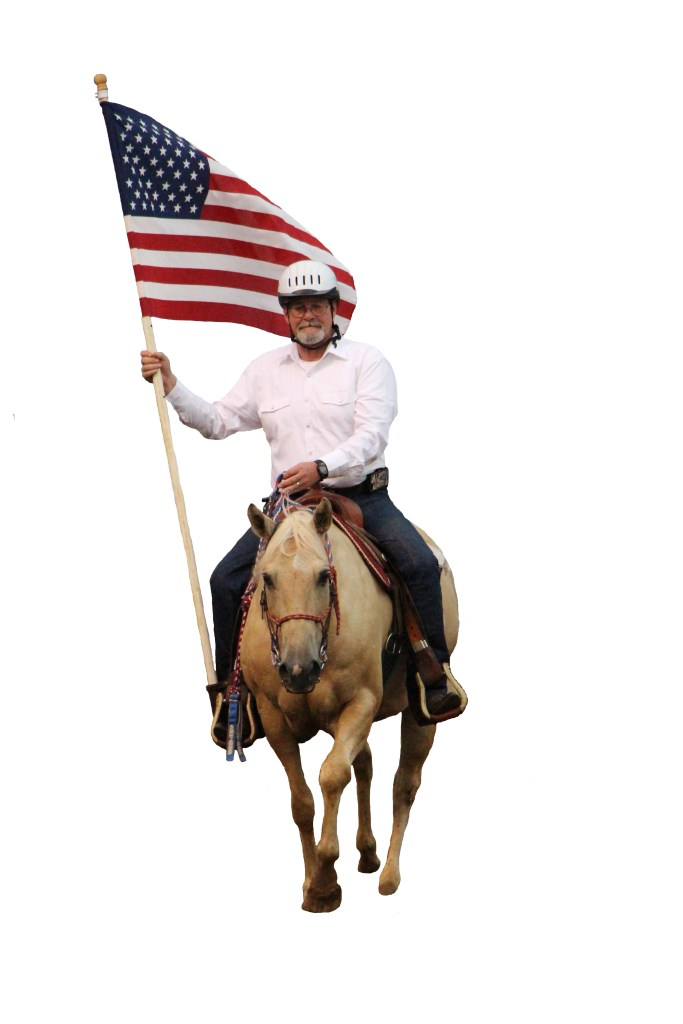 veteran carrying an American flag on a palomino horse
