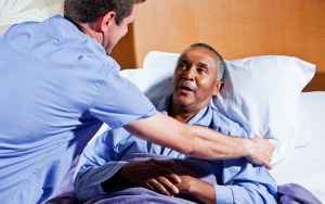 Male nurse (30s) helping African American senior man (60s) in hospital bed.