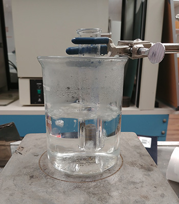 Beaker on a hot plate with a test tube containing the sample submerged in boiling water