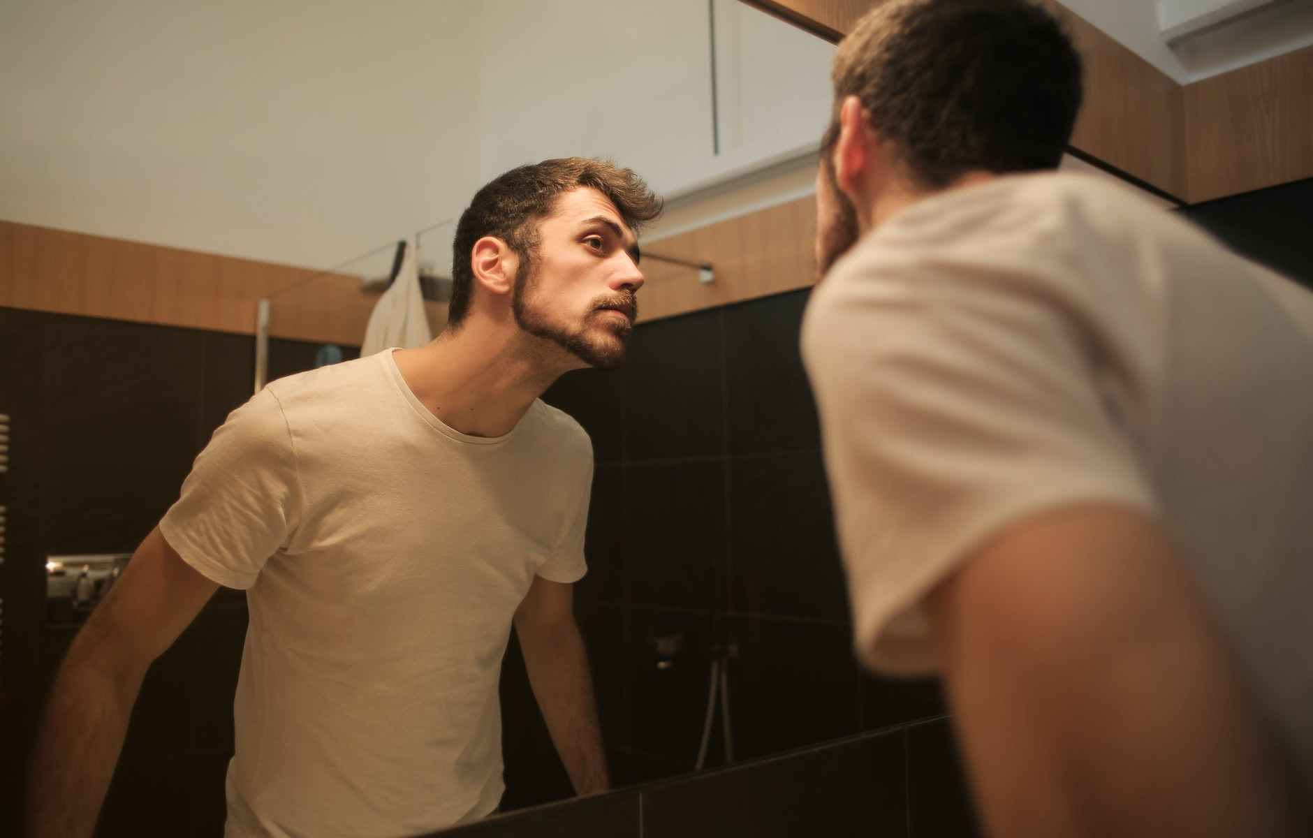 stylish concentrated man looking in mirror in bathroom