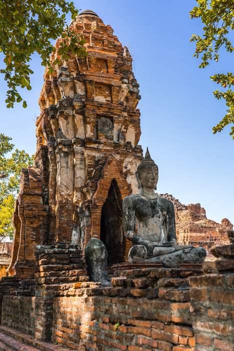 The ruins of Ayutthaya with a buddha in front, Ayutthaya day trip from Bangkok, Ayutthaya tour from Bangkok, Getting to Ayutthaya from Bangkok, Ayutthaya day tour from Bangkok, bus Bangkok to Ayutthaya, train Bangkok to Ayutthaya, how to get to Ayutthaya from Bangkok by train, day trip to Ayutthaya from Bangkok, Bangkok to Ayutthaya train, best day trip from Bangkok, Ayutthaya Day Trip From Bangkok, Thailand