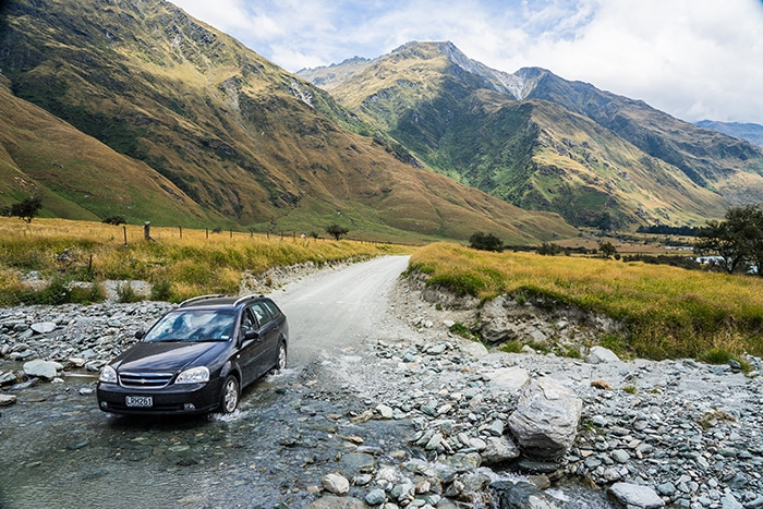 Driving a car through a ford in the Mountains of New Zealand. (day trips from Christchurch, Christchurch day trips, places to visit near Christchurch, things to do in Canterbury New Zealand, visit Christchurch)