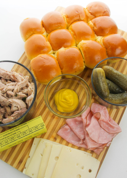 Ingredients for cuban sliders on a cutting board - sheet buns, pickles, mustard, butter, ham, sliced slice cheese and stick of butter