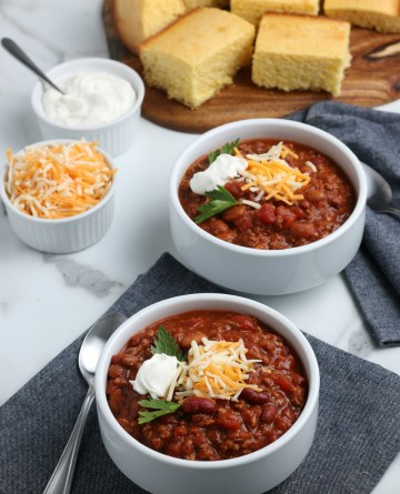 2 bowls of chili topped with shredded cheese and sour cream