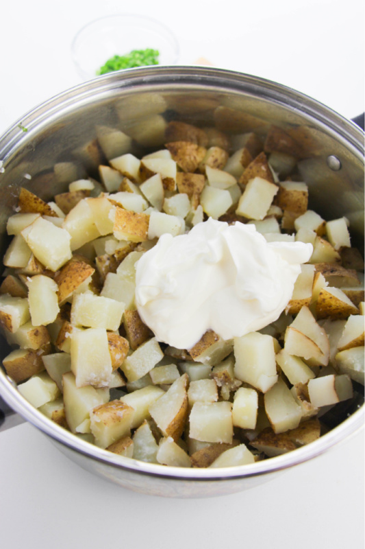 adding sour cream, milk and butter to the potatoes