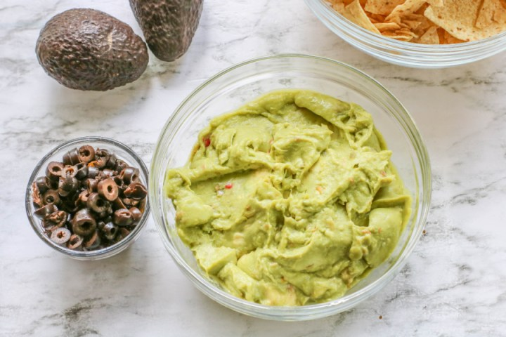 guacamole in a glass bowl and a small bowl of sliced black olives