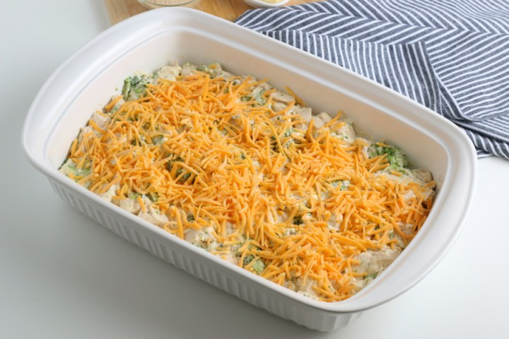 chicken mixture in a baking dish topped with shredded cheese
